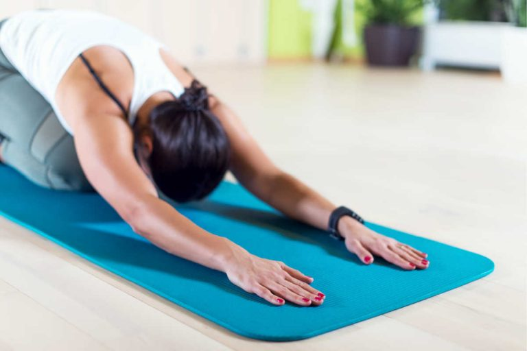 the best yoga mats for sweaty hands woman on blue yoga mat doing childs pose
