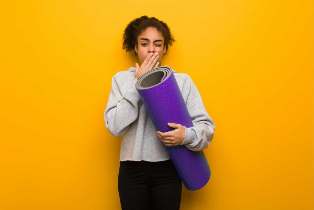 why does yoga make you yawn woman holding purple yoga mat and yawning